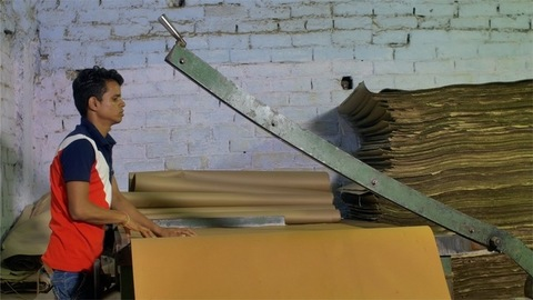 Young worker cutting paper roll using a manual guillotine paper cutting machine