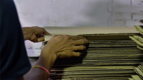 Closeup of Indian workers pilling up the pieces of cardboard in the warehouse