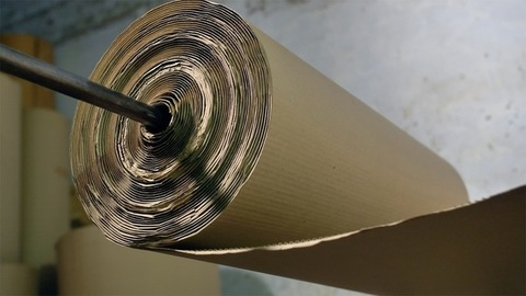 Closeup shot of a cardboard paper roll being pulled to make cardboard boxes