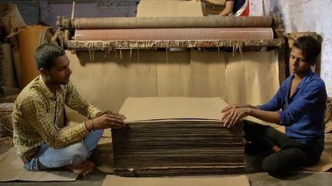 Two Indian workers collecting cardboard sheets from roller pasting machine