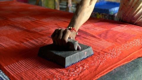 Shot of man block printing on a cotton fabric