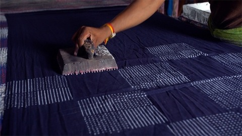 A block printing artist working at a textile workshop