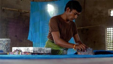 Block Printing - A man adjusting the blue cloth for block printing