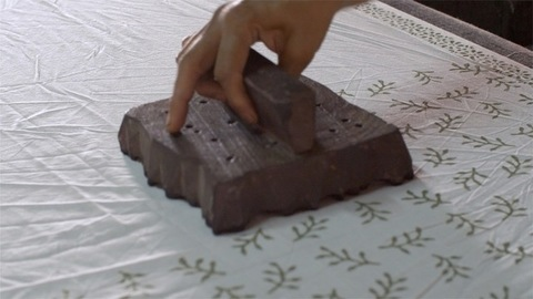 Closeup shot of a man block printing with woodblock in a fabric