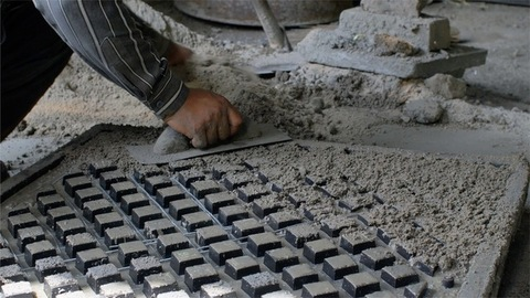 Closeup shot of a worker adding cement to the frame of ventilator