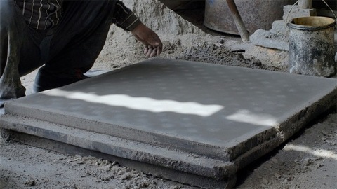 Indian worker making the concrete surface smooth using a float hand tool