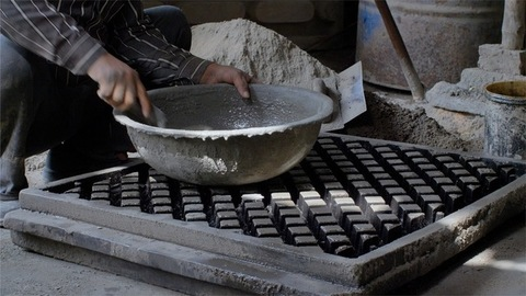Indian worker mixing cement and water in an iron head pan using a trowel