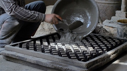 Hands of a laborer making ventilated bricks made of cement using a float hand tool