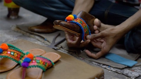 Cobbler making a beautiful bright colored sandal