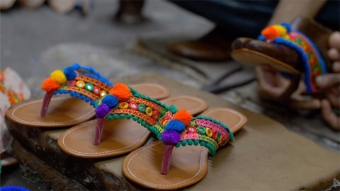 Shoemaker joining the straps of the sandal