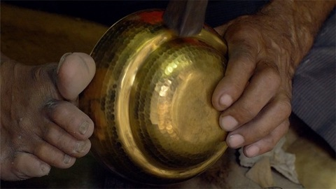 Shot of a skilled Indian craftsman designing and shaping a metal utensil with the hammer