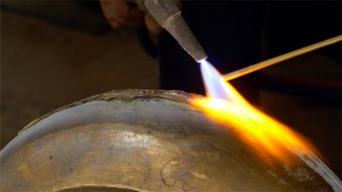 A labourer / worker sealing the joints of brass metal utensils in his workshop