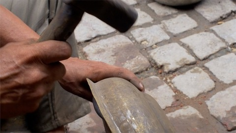 Coppersmith making traditional brass and copper utensils