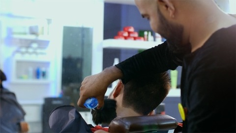 Backview shot of a male hipster getting a trendy hairstyle done by a hairstylist