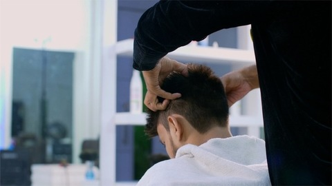 Professional hairdresser's hands giving a head massage to the male customer