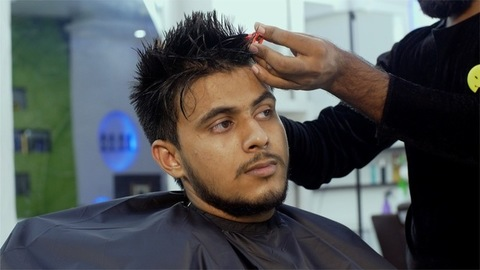 Handsome Indian guy getting a trendy haircut by a hairstylist in a unisex salon