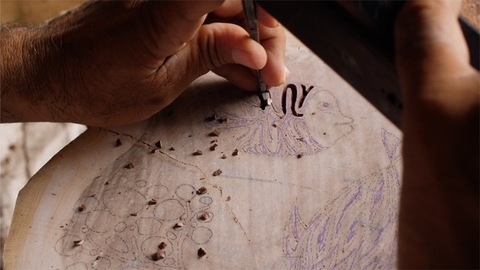 Block Printing - Indian artisanal carver creating a wood block stamp