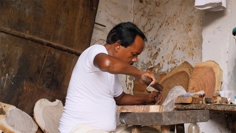 Block Printing - An Indian craftsman carving design with a chisel on a piece of wood