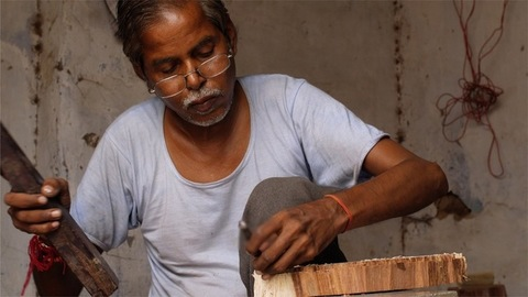 Block Printing - Indian worker carving design to make a wooden stamp