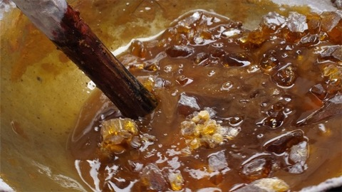 High angle shot of melting raw materials into a large kadhai to make lac sticks