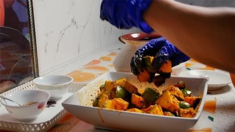 Woman transferring raw mango achar/pickle in a white ceramic pot