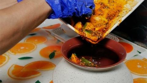 A woman transferring raw mango achar / pickle in a white ceramic pot
