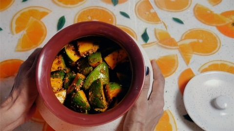 Shot of a woman tossing the pot full of raw mango pickle / achar