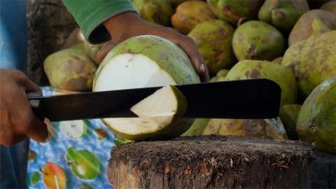 Closeup shot of an Indian vendor's hands cutting a coconut using a big knife