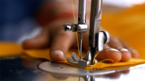 Hands of an Indian female tailor slowly working on a professional sewing machine