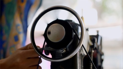 Tailor moving the wheel of a vintage sewing machine to start it's functioning