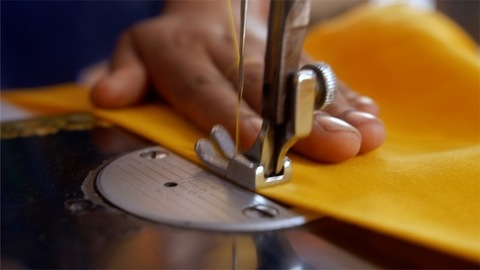 Closeup of sewing machine's needle rapidly moves up and down while stitching