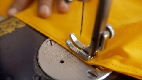 Hands of a worker using a professional sewing machine at a textile workshop
