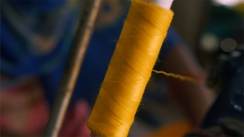 Closeup shot of a spool with thin yellow thread on a professional sewing machine