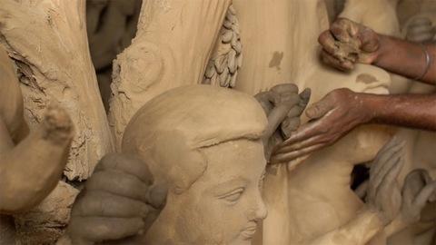 Indian artist shaping the hand of a clay sculpture/statue of Hindu God Kartikeya