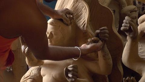 Hands of an Indian artist making clay sculptures of Hindu idol Goddess Durga