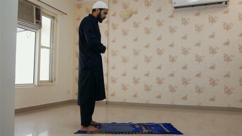 Muslim man wearing kufi prostrating and worshiping Allah on the carpet at home