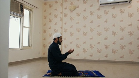 Indian Muslim guy wearing kufi bowing his head while offering prayers to god