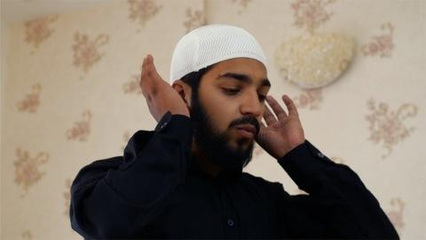 Closeup shot of a Muslim man wearing kufi offering prayers to Allah - EID festival