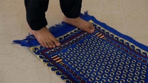 Closeup shot of a young Muslim man's feet standing on a prayer mat in India
