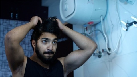Shaggy young guy combs his hair with hands in the bathroom - lifestyle concept
