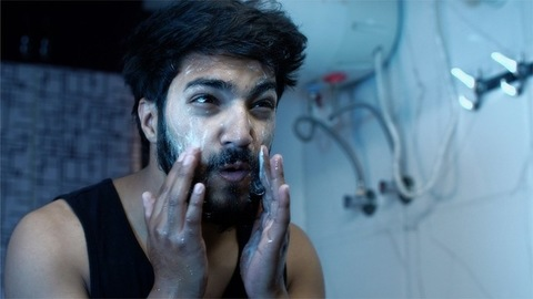 Shot of a boy with thick beard applying and cleaning his face with face wash / soap