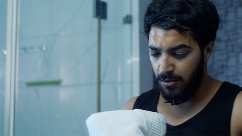 Handsome young Indian boy wiping his face with a white towel - clean hygienic