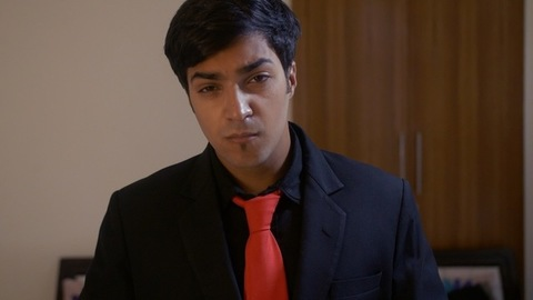 Handsome Indian man getting dressed up for party looking in the mirror