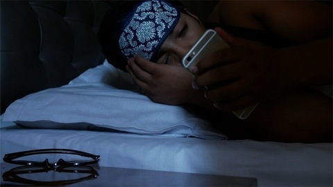Smart Indian young man sleeping with a blindfold, wake up and turn off the alarm on mobile phone