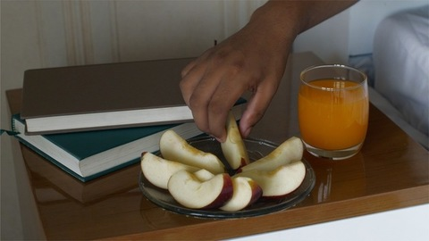 Close-up shot of bedside table with a plate full of apple slices, books and a juice glass