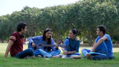 Beautiful Indian girl playing guitar while sitting with her friends after class