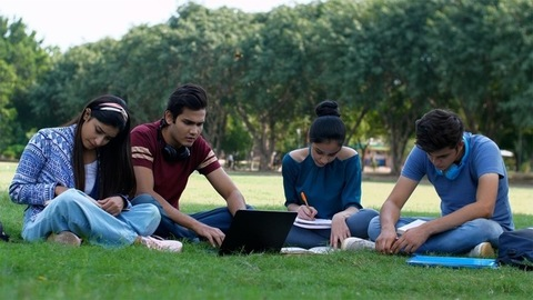 Group of Indian teenagers studying together using books and laptop - college life