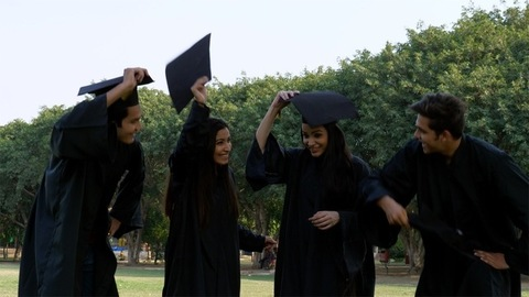 Young happy graduates throwing their graduation hats in the air - celebration time