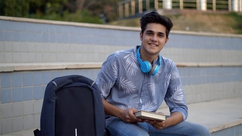 Cute Indian boy smiling at the camera with a book in his hand - confident look