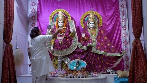 Tilt shot of an Indian priest doing Aarti of Lord Vishnu and Goddess Lakshmi in temple